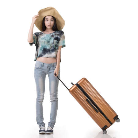 dragging: Exciting Asian woman drag a luggage, full length portrait isolated on white background. Stock Photo