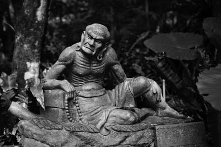 arhat: Old ruined Arhat Kanakbharadvaja statue in forest, Taiwan, Asia.