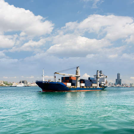 freighter: Freighter with cargo sailing on sea with blue sky and green water and beautiful cityscape of buildings and skyscraper in Kaohsiung, Taiwan.