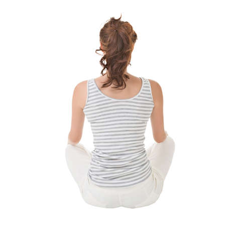 back ground: Attractive asian woman sitting on the ground. Rear view. Full length portrait with copyspace of white wall.
