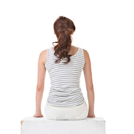 mujer sentada: Atractiva mujer asiática sentada en el suelo. Vista trasera. Retrato de cuerpo entero con copyspace de pared blanca. Foto de archivo