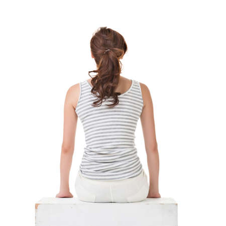 sitting on the ground: Attractive asian woman sitting on the ground. Rear view. Full length portrait with copyspace of white wall.