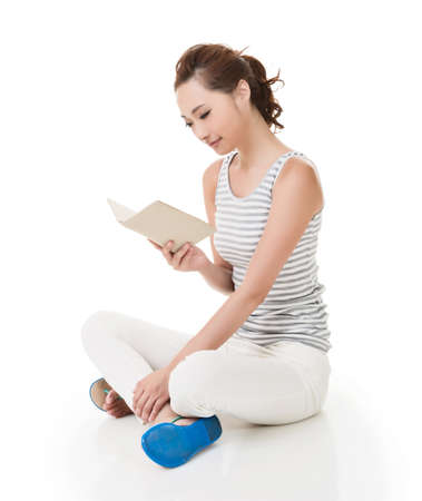 sitting on the ground: Young woman sit on ground and read a book, full length portrait isolated on white background.