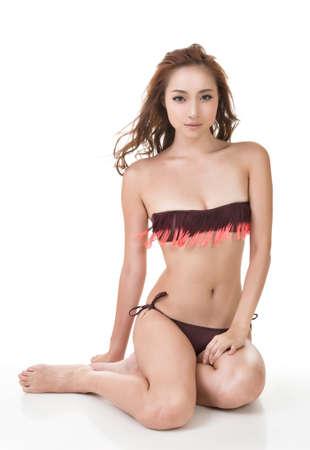 Sexy Asian bikini woman sit on studio white ground. photo