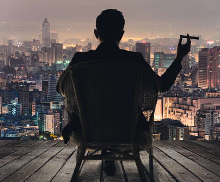 rich man: Silhouette of businessman sit on chair and hold a cigar and looking at the city in night. Stock Photo