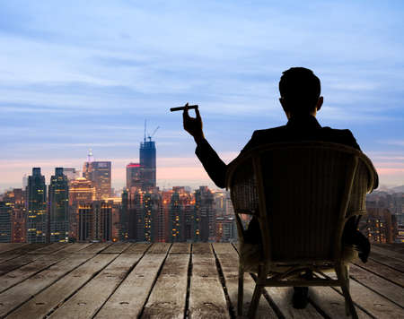 man: Silhouette of businessman sit on chair and hold a cigar and looking at the city in night. Stock Photo