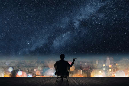 Silhouette of businessman sit on chair and hold a cigar unger the stars.