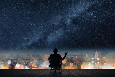 estrella: Silueta del hombre de negocios se sienta en silla y mantenga un cigarro unger las estrellas.
