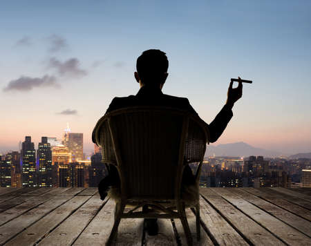 Silhouette of businessman sit on chair and hold a cigar and looking at the city in night. 免版税图像
