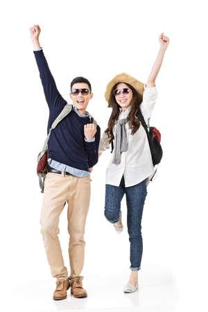 アジア系の若いカップルを旅行エキサイティングなダンス、白い背景上に分離されて完全な長さの肖像画を感じる。