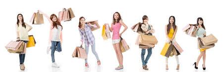 chicas comprando: Las mujeres asi�ticas atractivas compras y sosteniendo bolsas, retrato de cuerpo entero aisladas sobre fondo blanco.