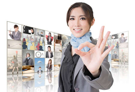 ok sign: Confident Asian business woman give you a okay sign standing in front of TV screen wall, closeup portrait.