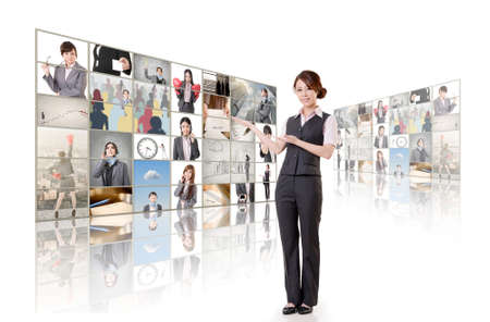 tv wall: Business woman introduce and standing in front of TV screen wall. Stock Photo