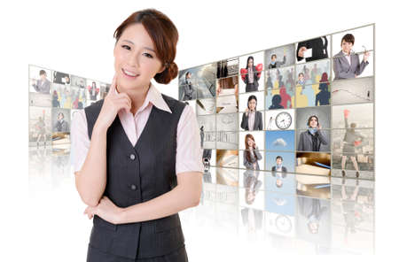 tv wall: Attractive Asian business woman standing in front of TV screen wall, closeup portrait. Stock Photo