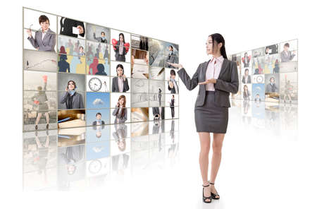 introduce: Business woman introduce and standing in front of TV screen wall. Stock Photo