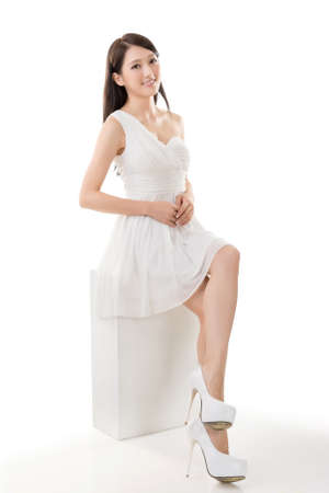 Attractive young Asian beauty in white dress sit on a box, full length portrait isolated on white. Stock Photo