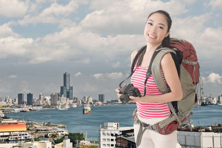avocation: Happy smiling Asian young female backpacker with camera standing in front of Kaohsiung harbor, Taiwan