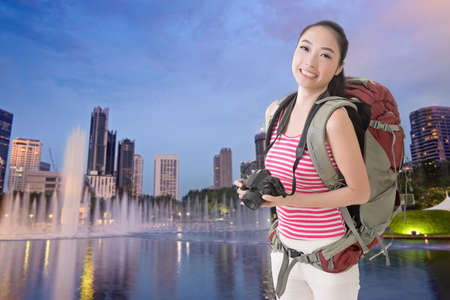avocation: Happy smiling Asian young female backpacker with camera standing in front of skyscrapers in Kuala Lumpur, Malaysia.