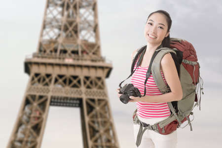 avocation: Happy smiling Asian young female backpacker with camera standing in front of Eiffel tower in Paris.