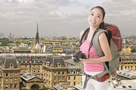 sightsee: Happy smiling Asian young female backpacker with camera standing in front of skyline of Paris.
