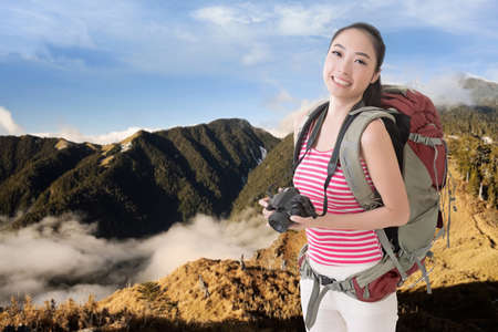avocation: Happy smiling Asian young female backpacker with camera standing in front of mountains.