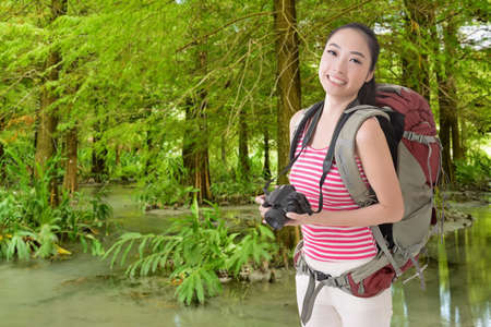 avocation: Happy smiling Asian young female backpacker with camera in the forest. Stock Photo