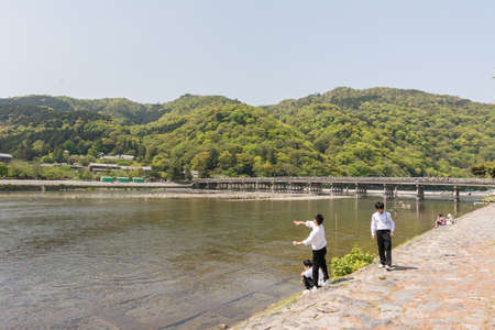 aisa: KYOTO, JAPAN - APRIL 26th  : Students throw stones at the shore of Hozu (Katsuragawa) River in Arashiyama in Kyoto, Japan on 26th April 2014.
