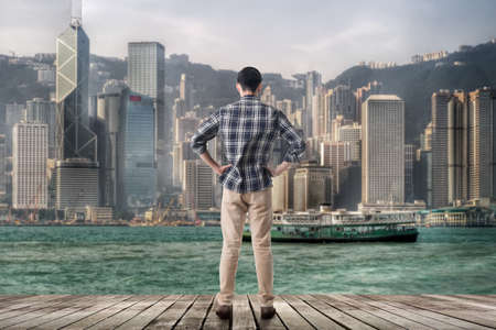 Asian man standing and looking the skyline of the Hong Kong city photo