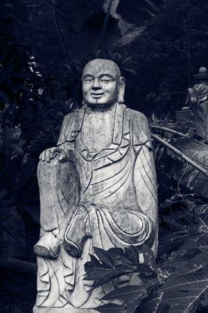 venerable: Ruined stone statue Ksitigarbha Bodhisattva in garden.