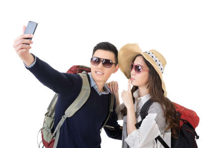 Asian young traveling couple selfie, full length portrait isolated on white background.