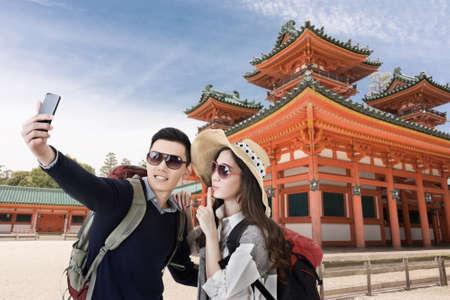 Asian couple travel and selfie in Heian Jingu Shrine, Kyoto, Japan. photo