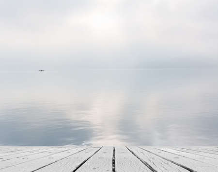 heave: Lake with mist and cloud, focus on wooden desk table.