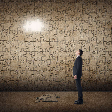mystery man: Asian man standing in front of a puzzle wall. Concept of mystery, problem, solution. Stock Photo