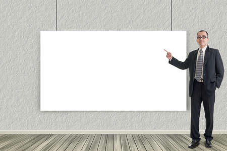 introduce: Asian business man introduce with blank board in a room. Stock Photo