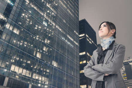 Confident Asian business woman stand and think, closeup portrait with office building background. photo