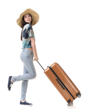 Exciting Asian woman drag a luggage, full length portrait isolated on white background. 免版税图像