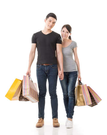 Asian couple shopping, full length portrait isolated on white background. photo