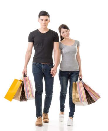 Asian couple shopping, full length portrait isolated on white background.