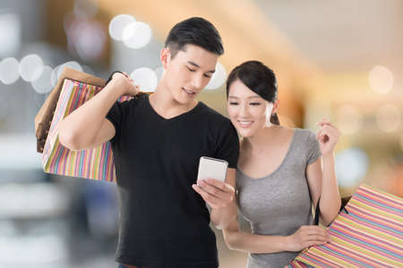 Young Asian couple shopping and looking at cellphone, closeup portrait. photo