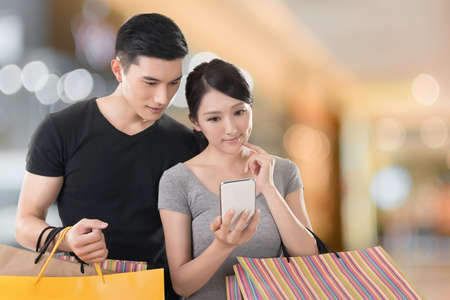 handphone: Young Asian couple shopping and looking at cellphone, closeup portrait.