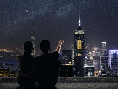 urban scenics: Silhouette of couple sit on ground point faraway on the roof above the city in the night. Stock Photo