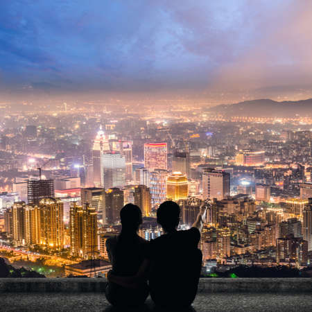 romantic love: Silhouette of couple sit on ground point faraway on the roof above the city in the night. Stock Photo