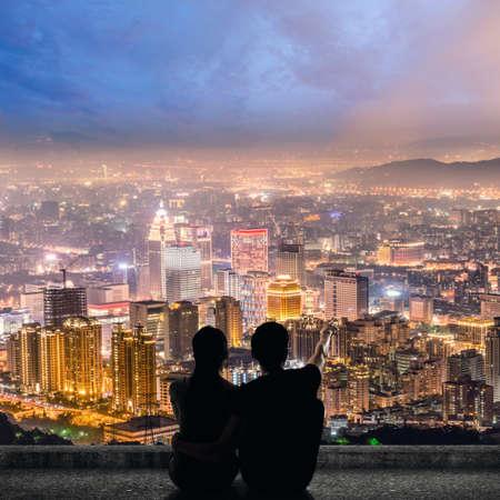 lejos: Silueta de la pareja se sientan en punto lejano del suelo en el techo por encima de la ciudad en la noche. Foto de archivo