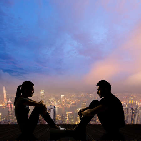 side by side: Silhouette of young couple face to face sit on ground in the city night.