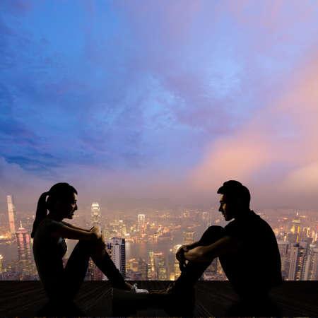 hombre romantico: Silueta de rostro joven pareja a enfrentar sentarse en el suelo en la ciudad de noche.