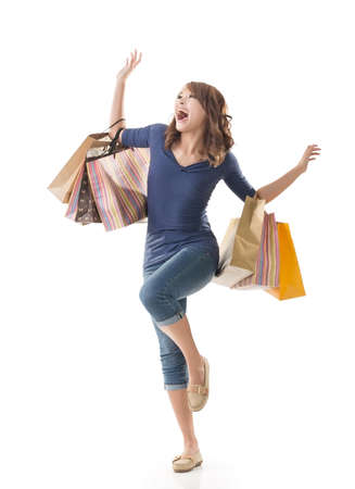 Cheerful shopping woman of Asian holding bags on white studio background. photo