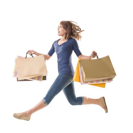 아시아 쇼핑 여자 점프, 화이트에 격리. 스톡 콘텐츠