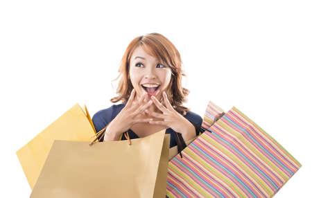 cara sorprendida: Alegre mujer de compras de las bolsas asiáticas que se sostienen en el fondo blanco del estudio.