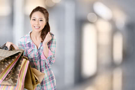 Exciting young shopping woman hold bags, closeup portrait with copyspace. photo