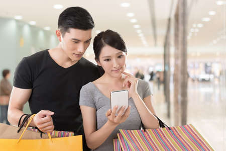 consider: Young Asian couple shopping and looking at cellphone, closeup portrait.